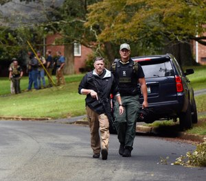 Law enforcement officers search the Foxhall neighborhood behind Mount Tabor High School in Winston-Salem, N.C., after a shooting that left one student dead, Wednesday, Sept. 1, 2021.