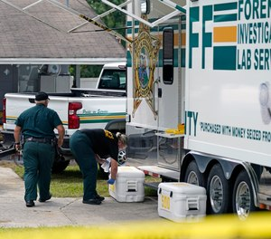 Officers from the Polk County Sheriff Department work outside Tuesday, Sept. 7, 2021, in Lakeland, Fla., at the home where a family of four was shot and killed.