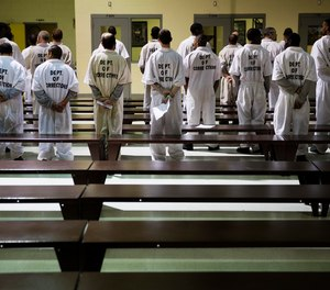 In this Dec. 1, 2015, file photo prisoners stand while being processed for intake at the Georgia Diagnostic and Classification Prison in Jackson, Ga.