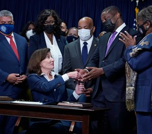 New York Gov. Kathy Hochul, seated, hands the first pen, during the signing of the