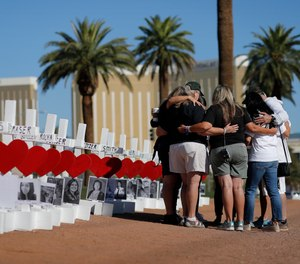 In this Oct. 1, 2019, file photo, people pray at a makeshift memorial for shooting victims in Las Vegas. People who died will be remembered Friday, Oct. 1, 2021, during the fourth anniversary of the massacre that became the deadliest mass shooting in modern U.S. history.