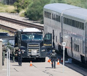 A Tucson Police Department SWAT truck is parked near the last two cars of an Amtrak train in downtown Tucson, Ariz., Monday, Oct. 4, 2021.