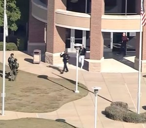 In this image from WFAA-TV video, law enforcement personnel arrive at Timberview High School on Wednesday in Arlington, Texas.