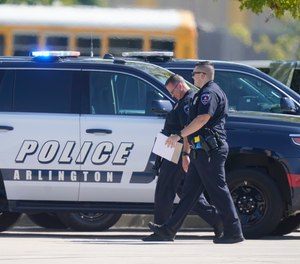 Law enforcement officers walk in the parking lot of Timberview High School after a shooting inside the school located in south Arlington, Texas, Wednesday, Oct. 6, 2021.