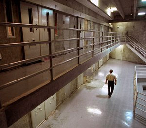 In this Oct. 28, 1999, file photo a correctional officer walks through a housing unit during a lockdown at California State Prison, Sacramento, in Folsom, Calif.