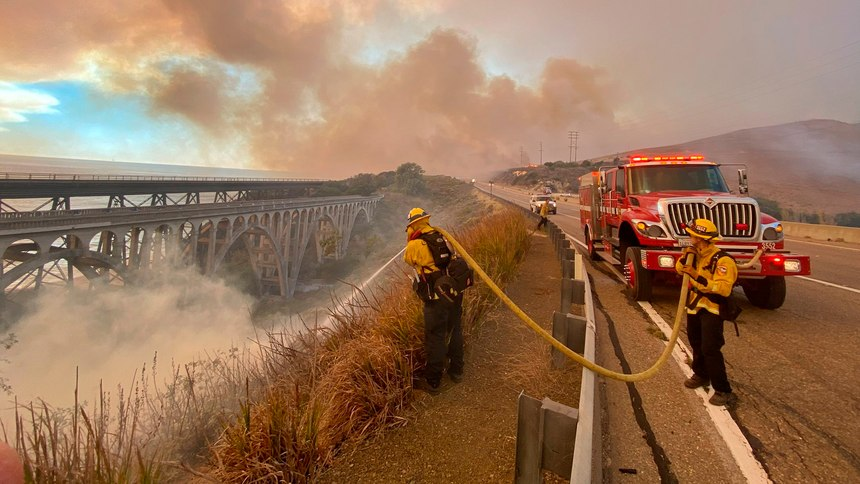 Firefighters extinguish flames Tuesday afternoon, Oct. 12, 2021, that have spotted ahead of the fire front along Highway 101 southbound at Vista Point, north of Refugio State Beach in Santa Barbara County, Calif.
