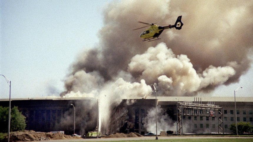 A helicopter flies over the Pentagon in Washington as smoke billows over the building immediate after the attack.
