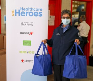 An FDNY EMS member holds her first care package of shelf-stable food, household cleaning and personal care products, as well as over-the-counter medicine, provided by NYC Healthcare Heroes.