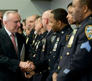 NYPD Commissioner William Bratton greets police officers as they arrive for a news conference, Tuesday, Feb. 23, 2016, abouta new tool that maps a week's worth of crime throughout the five boroughs.