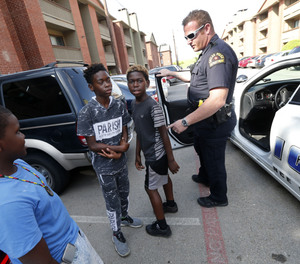 Dallas police sergeant A. P. Martin talks with kids while performing community patrol at the Cielo Ranch apartments in Southwest Dallas, Sunday, July 10, 2016.