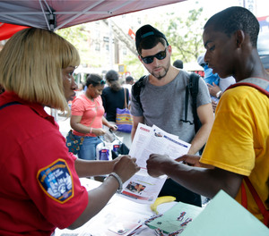 In this Saturday, Aug. 15, 2015 photo, emergency medical technician Janice Gardner, left, talks to Kenneth Worrell, left, 16, and Steven Vargas, 23, while working the recruitment table during a FDNY block party in the Harlem neighborhood of New York.