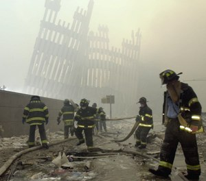 With the skeleton of the World Trade Center twin towers in the background, New York City firefighters work amid debris on Cortlandt St. after the terrorist attacks of Tuesday, Sept. 11, 2001. (AP Photo/Mark Lennihan)