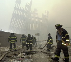 With the skeleton of the World Trade Center twin towers in the background, New York City firefighters work amid debris on Cortlandt St. after the terrorist attacks of Tuesday, Sept. 11, 2001.