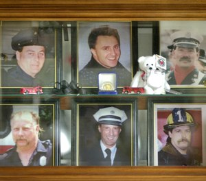 In this 2001 file photo, a display case in the lobby of the Worcester Fire Department Grove Street station memorializes six firefighters who were killed at the cold storage warehouse fire Dec. 3, 1999, in Worcester, Mass. Pictured from top left clockwise are firefighters Joseph McGuirk, James Lyons III, Jeremiah Lucey, Paul Brotherton, Lt. Thomas Spencer and Timothy Jackson. (AP Photo/Charles Krupa, File)