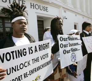 Supporters for a bill that would automatically restore voting rights to convicted felons upon their release from prison hold up signs supporting the bill during a news conference Thursday, Feb. 9, 2006, in front of the State House in Montgomery, Ala. (AP Photo/Rob Carr)