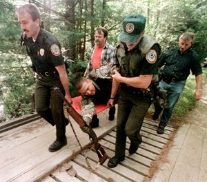 Wounded New Hampshire state trooper Jeffrey Caulder is carried out of the woods still holding his gun in Brunswick, Vt., Tuesday, Aug. 19, 1997, following a gun battle with Carl Drega.