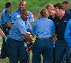 Emergency personnel carry a two-year-old boy to a waiting ambulance after he fell into White Oak Bayou in Houston on Thursday, Feb. 26, 2009. (AP Photo/Houston Chronicle, Steve Campbell)