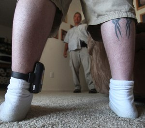 In this photo taken Monday, Aug. 3, 2009, Parole Agent Steve Nakamura talks with a parolee wearing a GPS locater worn on his ankle, in Sacramento, Calif.