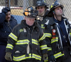 FDNY firefighters fire crews look up at the East 178th Street building where two firefighters were killed and others injured in an early morning fire in the Bronx. (AP Photo/Gregory Bull)