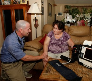 In this Aug. 31, 2011 photo, Eagle County paramedic Kevin Creek checks the pulse of Danielle Hefferan, 21, during a house call at her home in Eagle, Colo. (AP Photo/Ed Andrieski)