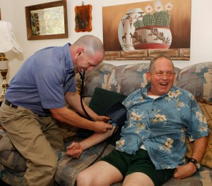 In this Aug. 31, 2011 photo, Eagle County paramedic Kevin Creek checks the blood pressure of James Duke, 64, during a house call to his home in Eagle, Colo. (AP Photo/Ed Andrieski)