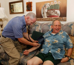In this Aug. 31, 2011 photo, Eagle County paramedic Kevin Creek checks the blood pressure of James Duke, 64, during a house call to his home in Eagle, Colo.