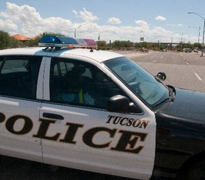 A police car blocks an entrance to Davis-Monthan Air Force Base in Tucson, Ariz., Friday, Sept. 16, 2011.