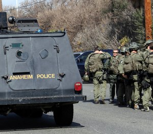 An Anaheim, Calif., police armored car and FBI SWAT team members gather near the perimeter of a bank standoff.