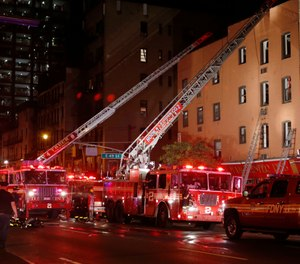 Fire truck ladders are extended to the roof of the site of a three-alarm fire in a four-story building on Manhattan's East side in New York, Wednesday, Sept. 17, 2014. (AP Photo/Kathy Willens)