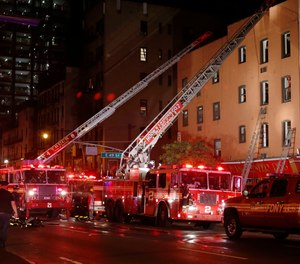 Fire truck ladders are extended to the roof of the site of a three-alarm fire in a four-story building on Manhattan's East side in New York, Wednesday, Sept. 17, 2014.