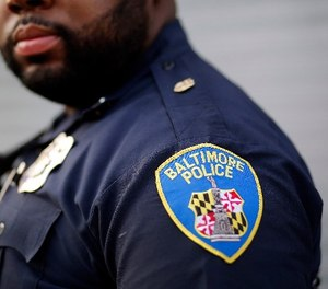 In this March 31, 2016, file photo, Baltimore Police Department Officer Jordan Distance stands on a street corner during a foot patrol in Baltimore.