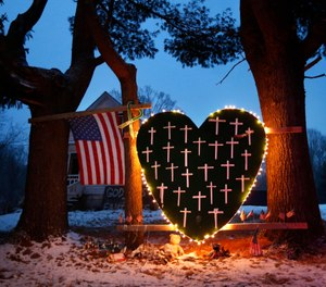 In this Dec. 14, 2013 file photo, a makeshift memorial with crosses for the victims of the Sandy Hook Elementary School shooting massacre stands outside a home in Newtown, Conn., on the one-year anniversary of the shootings. (AP Photo/Robert F. Bukaty, File)