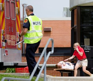 Volunteers participating in a training exercise for an active shooter simulate exiting the main entrance of Hopewell Elementary School with injuries Wednesday, May 25, 2016, in West Chester, Ohio.