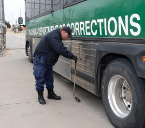 In this Jan. 24, 2013 file photo, a corrections uses a mirror to check the bottom of a transport bus leaving to take prisoners to other locations in the state at the Lexington Assessment and Reception Center, in Lexington, Okla. (AP Photo/Sue Ogrocki, File)