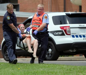 In a May 25, 2016 file photo, a volunteer with simulated injuries is carried during a training exercise for an active shooter at Hopewell Elementary School, in West Chester, Ohio.