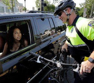 In this July 20, 2016 photo, police officer Matthew Monteiro speaks to a motorist about texting while driving while patrolling on his bicycle in West Bridgewater, Mass.