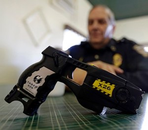 In this Nov. 14, 2013, file photo, a Taser X26 sits on a table in Knightstown, Ind.