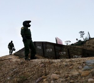 In this Wednesday, June 22, 2016, file photo, Border Patrol agents look over the primary fence separating Tijuana, Mexico, right, and San Diego in San Diego. (AP Photo/Gregory Bull, File)