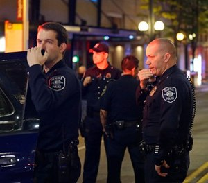 Police officers wait near a car near the scene of a shooting Wednesday, Nov. 9, 2016, in downtown Seattle. (AP Photo/Ted S. Warren)