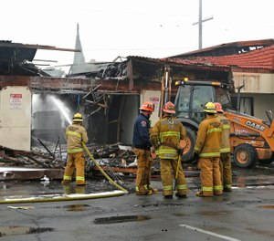 Firefighters battle a four-alarm fire at a strip mall in Monterey Park, Thursday, Dec. 15, 2016. (AP Photo/Nick Ut)