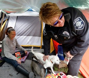 Homeless outreach is just one of the many activities police officers engage in to improve the quality of life of the citizens they serve. (AP Photo/Elaine Thompson)