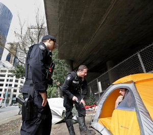 In this Thursday, March 23, 2017, file photo, Seattle police officers Wes Phillips, left, and Tori Newborn talk with Corvin Dobschutz as part of a team of outreach workers and officers that go out and connect homeless people to services.