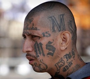 In this March 26, 2012 file photo a gang member of MS-13 attends mass at a prison in Ciudad Barrios, El Salvador.