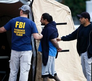 A man is taken into custody by FBI agents Wednesday, May 17, 2017, in Los Angeles. Hundreds of federal and local law enforcement fanned out across Los Angeles, serving arrest and search warrants as part of a three-year investigation into the violent and brutal street gang MS-13. (AP Photo/Jae C. Hong)