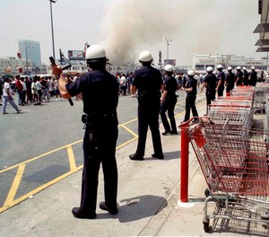 In this April 30, 1992 file photo, Los Angeles police form a line to prevent a crowd from going into a building in a day of fires and looting in Los Angeles.