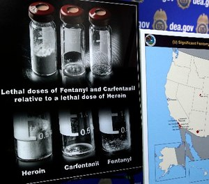 Posters comparing lethal amounts of heroin, fentanyl, and carfentanil, are on display during a news conference about the dangers of fentanyl, at DEA Headquarters in Arlington, Va.