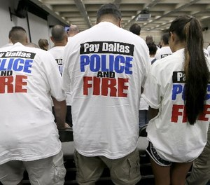 This file photo made Tuesday, Aug. 9, 2016, Dallas police and firefighters fill the gallery for a city council budget meeting at Dallas City Hall in Dallas.