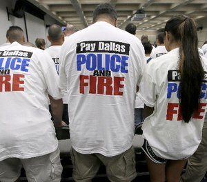 This file photo made Tuesday, Aug. 9, 2016, Dallas police and firefighters fill the gallery for a city council budget meeting at Dallas City Hall in Dallas. (AP Photo/LM Otero)