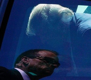 A Secret service agents is reflected in the window as President Donald Trump gets into his vehicle at General Mitchell International Airport Tuesday, June 13, 2017, in Milwaukee. (AP Photo/Morry Gash)