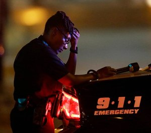 In this July 8, 2016, file photo, a Dallas police officer takes a moment as she guards an intersection in the early morning after an ambush on officers in downtown Dallas. (AP Photo/LM Otero, File)